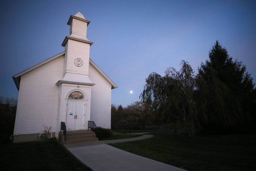 The moon rises behind Zion Church, built in 1881, at the Madison County Historical Society on October 29, 2020 in Winterset, Iowa. (Mario Tama/Getty Images)