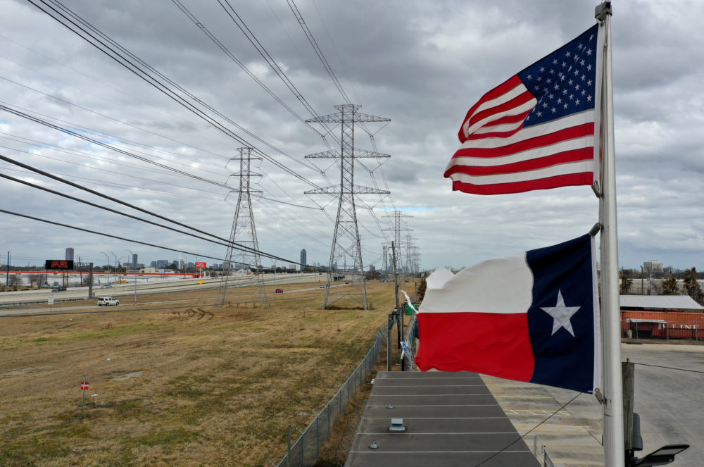 The U.S. and Texas flags fly in front of high voltage transmission towers on Feb. 21, 2021 in Houston, Texas. (Justin Sullivan/Getty Images)