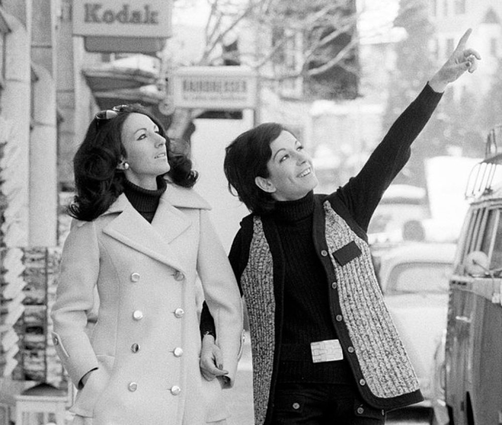 Two women walking arm in arm and watching something on the other side of the road. Sankt Moritz, March 1969 (Getty Images)