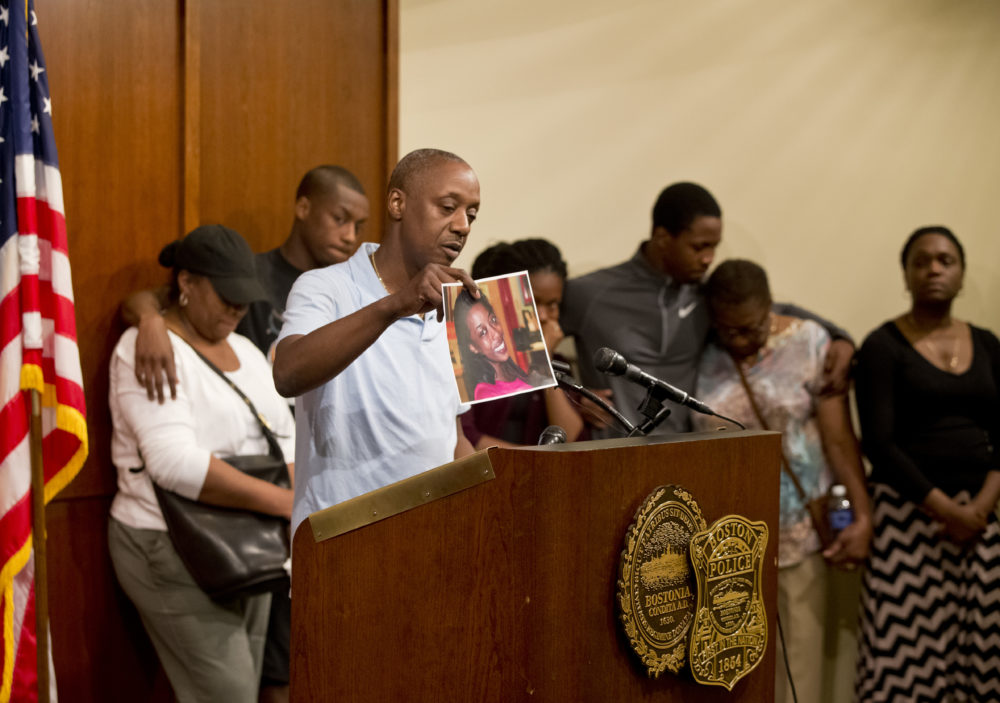 In this file photo from 2014, Ian Jaffier holds a picture of his daughter, Dawnn Jaffier, 26, who was fatally shot on Blue Hill Avenue that year. (Matthew J. Lee/The Boston Globe via Getty Images)