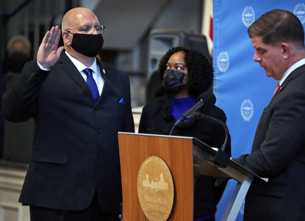 Dennis White, left, was sworn in by Mayor Marty Walsh, right, as the city's new police commissioner. White's wife, Jackie, stands off to White's left. (Jim Davis/Boston Globe)