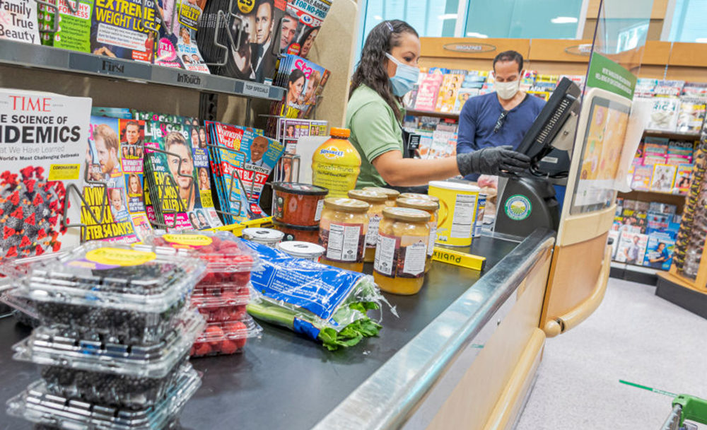 A Publix grocery store cashier and customer in Florida wear face masks and gloves. (Jeffrey Greenberg/Education Images/Universal Images Group via Getty Images)