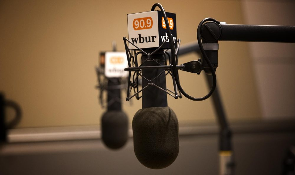 Microphones show the WBUR logo in a studio