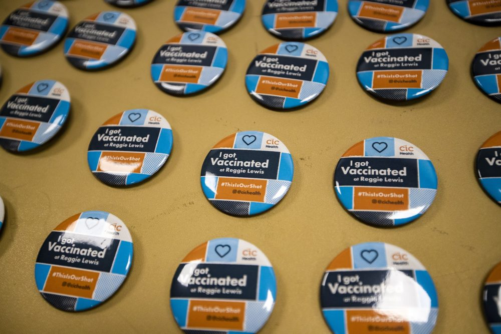 """""""I got vaccinated"""" buttons on a table for recipients of the Pfizer BioNTech vaccine to take on their way out of the Reggie Lewis Center. (Jesse Costa/WBUR)"""