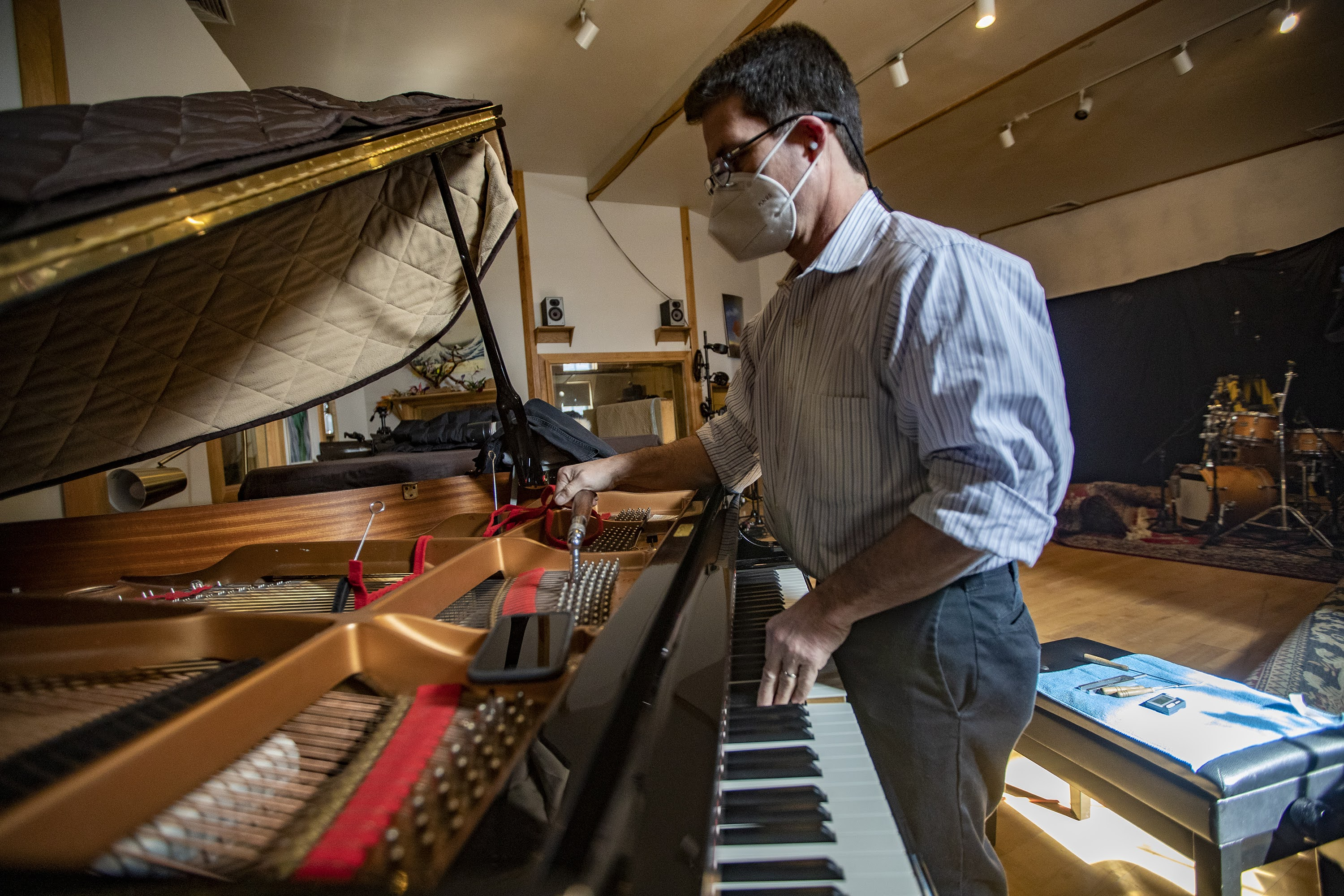 Fred Mudge uses a tuning hammer to tune a Yamaha C7 piano at the Wellspring Studio in Acton. (Jesse Costa/WBUR)