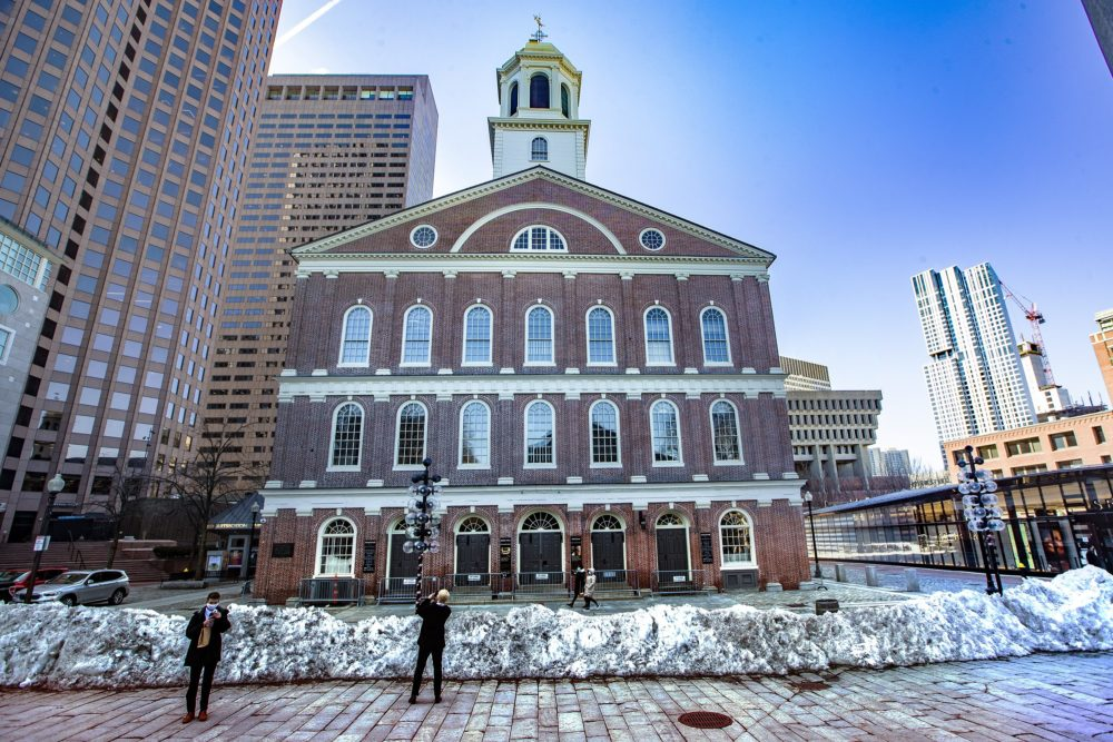 A couple of tourists stop to take phone pictures of Faneuil Hall. (Jesse Costa/WBUR)