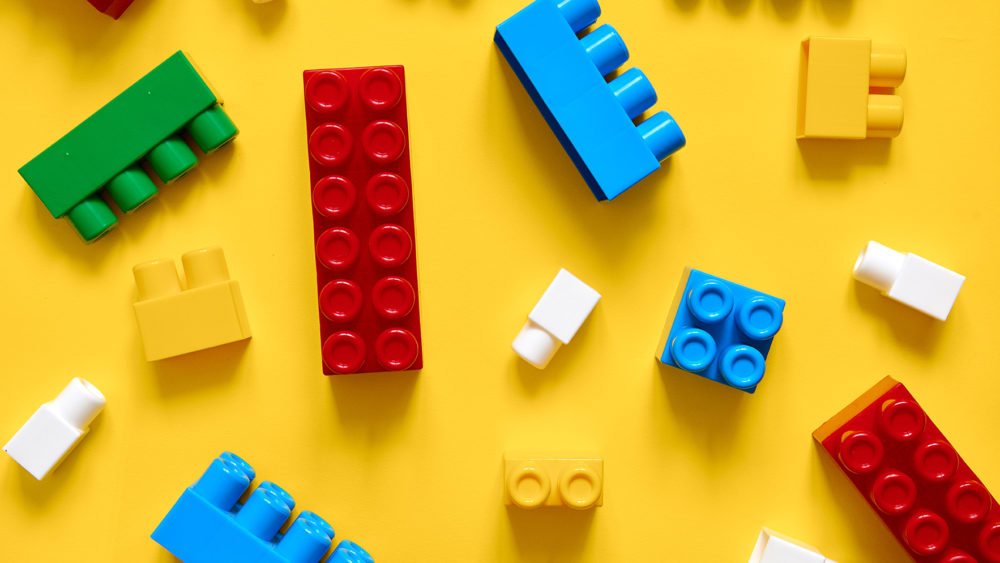 Colorful plastic building blocks flat lay on a yellow background.