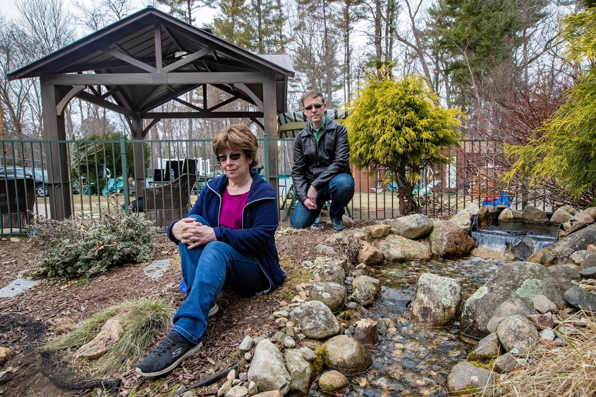 Lee Brooks lost her son to leukemia, and Brian Dellascio had Hodgkin lymphoma as a teen. They're pictured outside Brooks' Wilmington home. (Jesse Costa/WBUR)