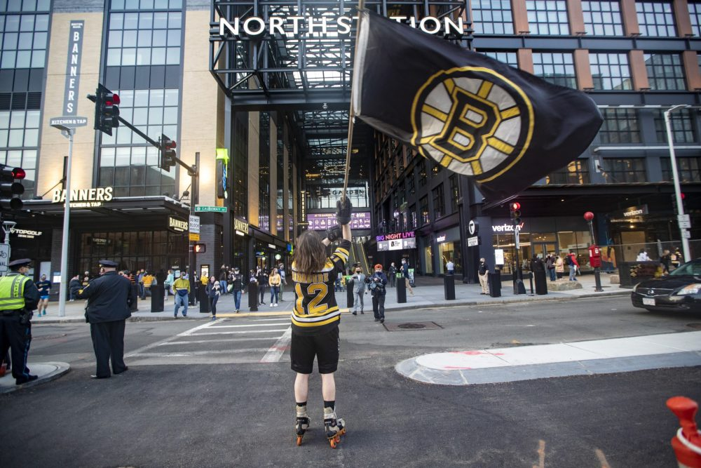 A man waves a Bruins flag on Causeway Street, in front of the entrance of TD Garden before the Bruins/Islanders game, the first game open to the public now that stadiums and arenas are permitted to hold up to 12% capacity since they were restricted by COVID-19 protocols. (Jesse Costa/WBUR)