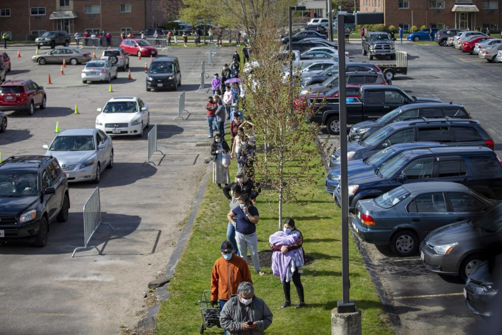 The line for food extends out of the parking lot and down Pond Street at a food pantry at St. Mary Parish in Waltham in May 2020. (Jesse Costa/WBUR)