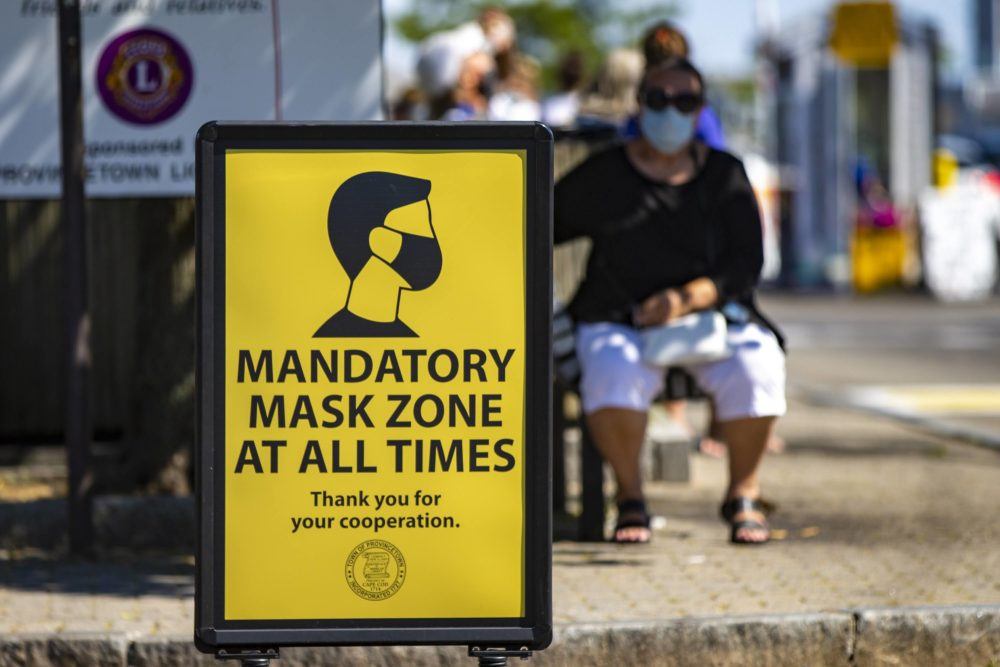 In this July 2020 photo, signs are posted around the business district of Provincetown reminding people to wear a mask in public to help prevent the spread of coronavirus. (Jesse Costa/WBUR)