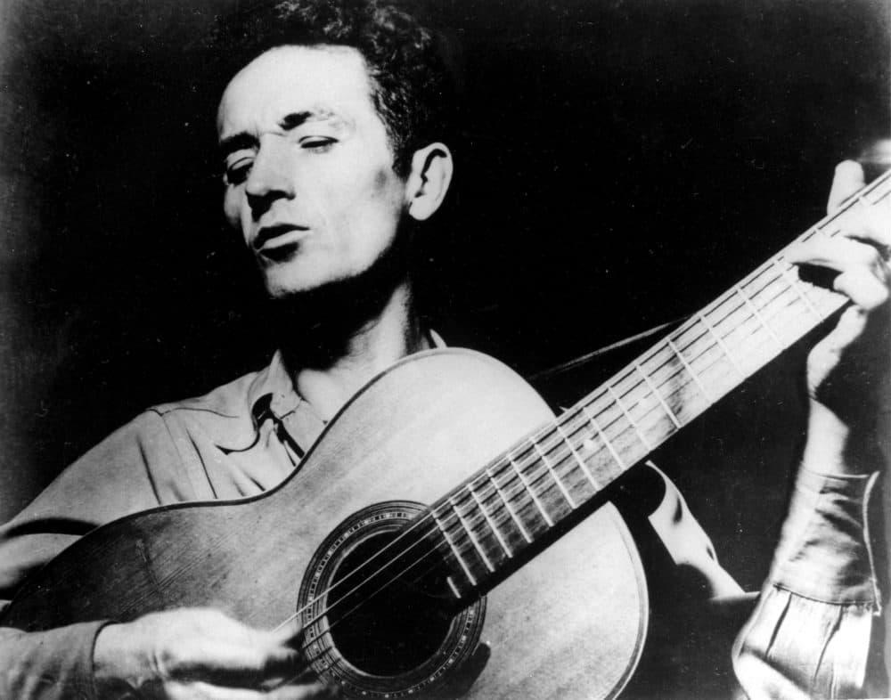 Folk singer Woody Guthrie plays his guitar. (AP Photo)