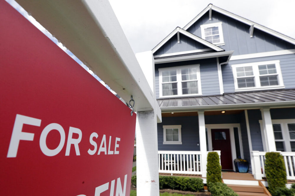 """A """"For Sale"""" sign stands in front of a home that is in the process of being sold in Monroe, Wash., outside of Seattle. (Elaine Thompson, File/AP Photo)"""