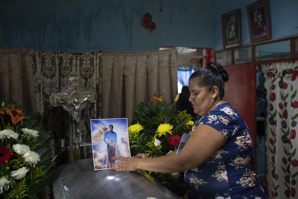 A woman places a photo of slain journalist Julio Valdivia on his casket during a wake for him inside his home in Tezonapa, Mexico, on Sept. 10, 2020. Valdivia's decapitated body was found five miles from Tezonapa a day earlier, and is at least the third reporter killed in the area since 2015. (Felix Marquez/AP)