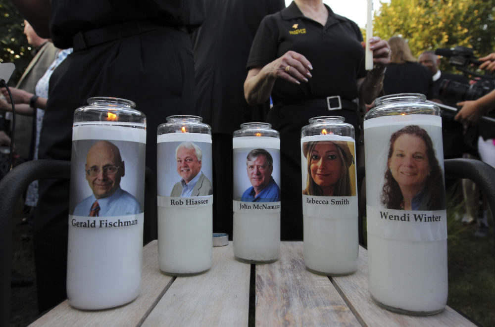 Fiveve employees of the Capital Gazette newspaper adorn candles during a vigil across the street from where they were slain in the newsroom in Annapolis, Md. (Jose Luis Magana/AP)