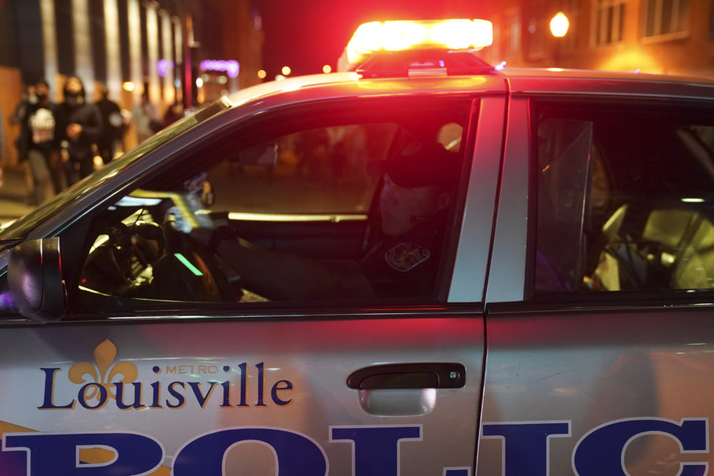 A police officer observes protesters, on Sept. 24, 2020, in Louisville, Ky. Protests in the city erupted followed the decision not to charge officers for killing Breonna Taylor. (John Minchillo/AP)