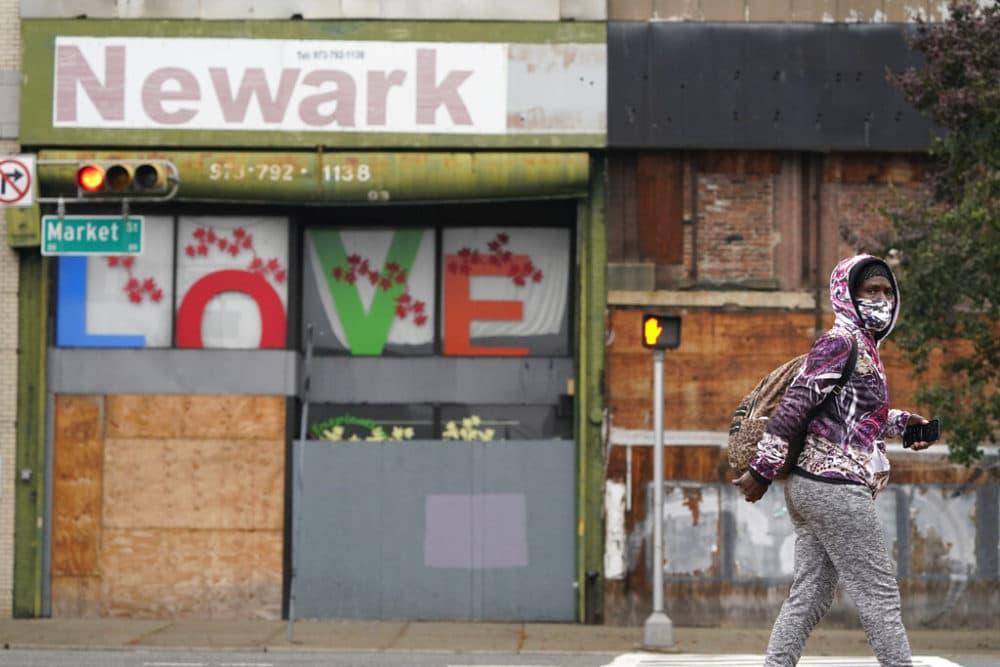 A pedestrian wears a mask as they walk through Newark, N.J., Monday, Oct. 26, 2020.  (AP Photo/Seth Wenig)
