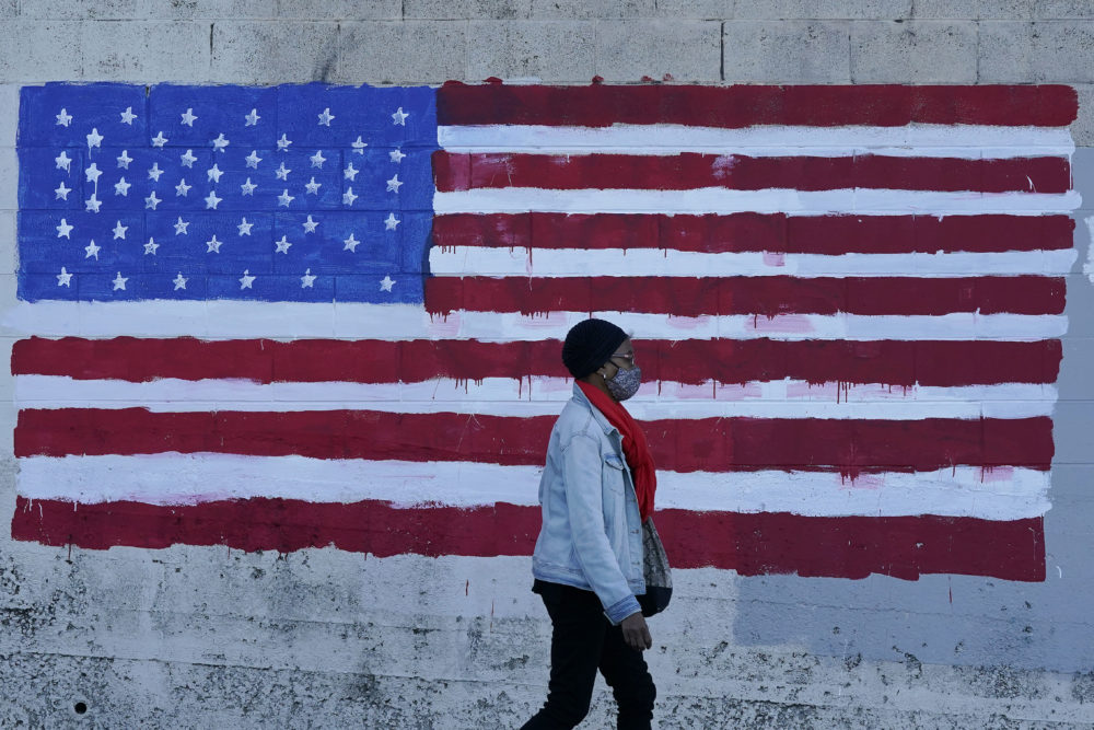 A woman wears a mask while walking past an American flag painted on a wall. (Jeff Chiu/AP)