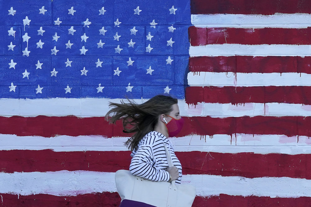A woman wears a mask while walking past a U.S. flag painted on a wall during the pandemic in San Francisco on Nov. 16, 2020. (Jeff Chiu/AP)