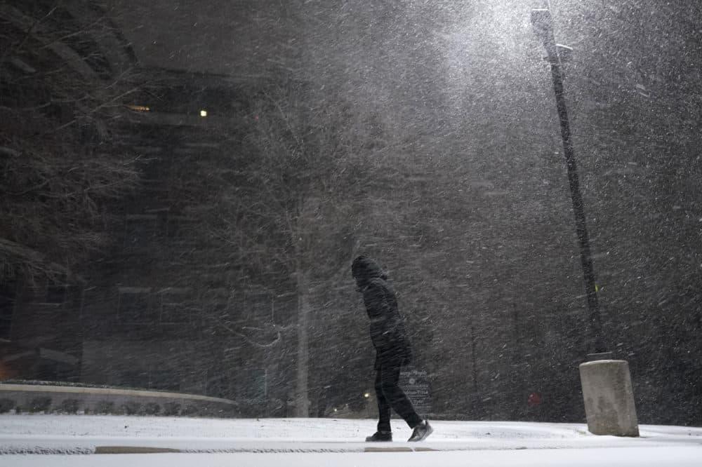 A woman walks through falling snow in San Antonio, Texas, on Sunday, Feb. 14, 2021. (Eric Gay/AP)