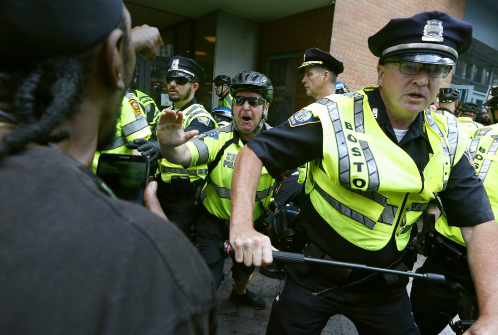 """In this Aug. 19, 2017, file photo, counterprotesters clash with police following a """"Free Speech"""" rally staged by conservative activists in Boston. (Michael Dwyer/AP File)"""