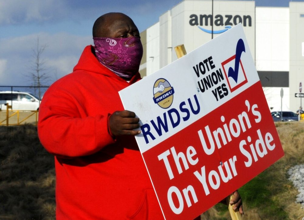 Michael Foster of the Retail, Wholesale and Department Store Union holds a sign outside an Amazon facility where labor is trying to organize workers on Tuesday, Feb. 9, 2021. (AP Photo/Jay Reeves, file)