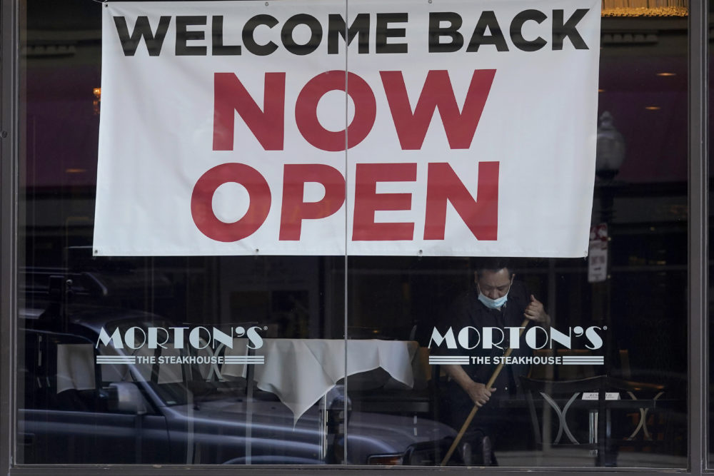 "In this March 4, 2021, file photo, a sign reading ""Welcome Back Now Open"" is posted on the window of a Morton's Steakhouse restaurant as a man works inside during the coronavirus pandemic in San Francisco. (Jeff Chiu/AP File)"