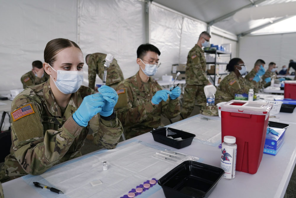 In this March 9, 2021, file photo, Army health specialists fill syringes with the Pfizer COVID-19 vaccine in Miami. Despite the clamor to speed up the U.S. vaccination drive against COVID-19, the first three months of the rollout suggest faster is not necessarily better. (Marta Lavandier/AP File)