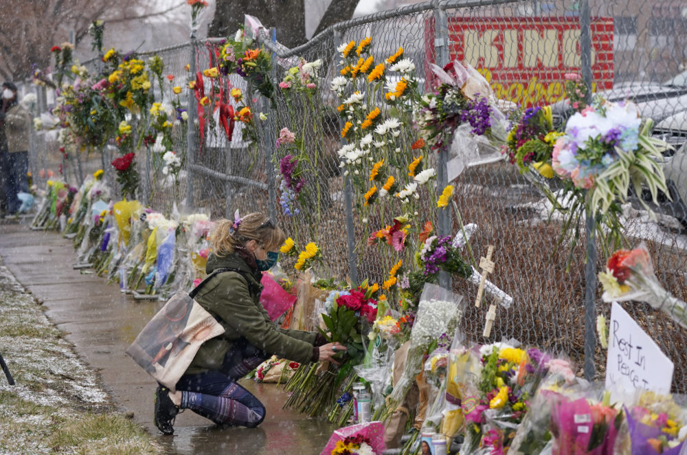 A mourner leaves a bouquet of flowers along a fence put up around the parking lot where a mass shooting took place in a King Soopers grocery store on Tuesday, March 23, 2021, in Boulder, Colo. (David Zalubowski/AP)