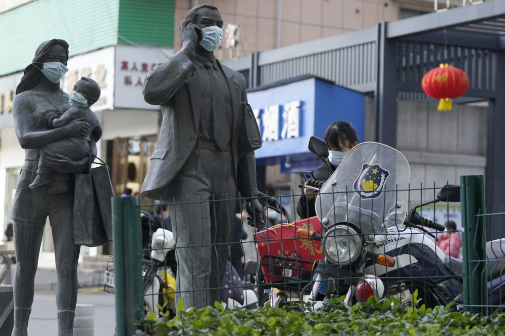 Statues along a street are seen with masks placed on them as a WHO mission visits Wuhan in central China's Hubei province