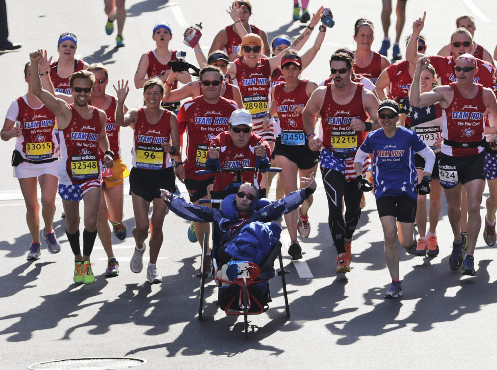 Dick and Rick Hoyt cross the finish line surrounded by supporters in the 118th Boston Marathon in Boston. (Charles Krupa/AP)