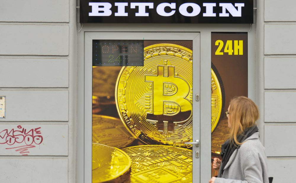 A woman passes in front of a Bitcoin exchange shop on April 4, 2018, in Krakow, Poland. (Artur Widak/NurPhoto via Getty)