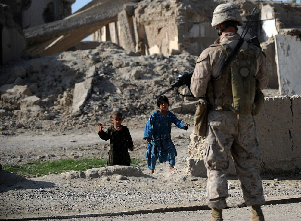 Afghan children watch as a US Marine from 2nd Battalion, 1st Marines Regiment stands in front of ruins in Garmser, Helmand Province, on March 13, 2011. (Adek Berry/AFP via Getty Images)