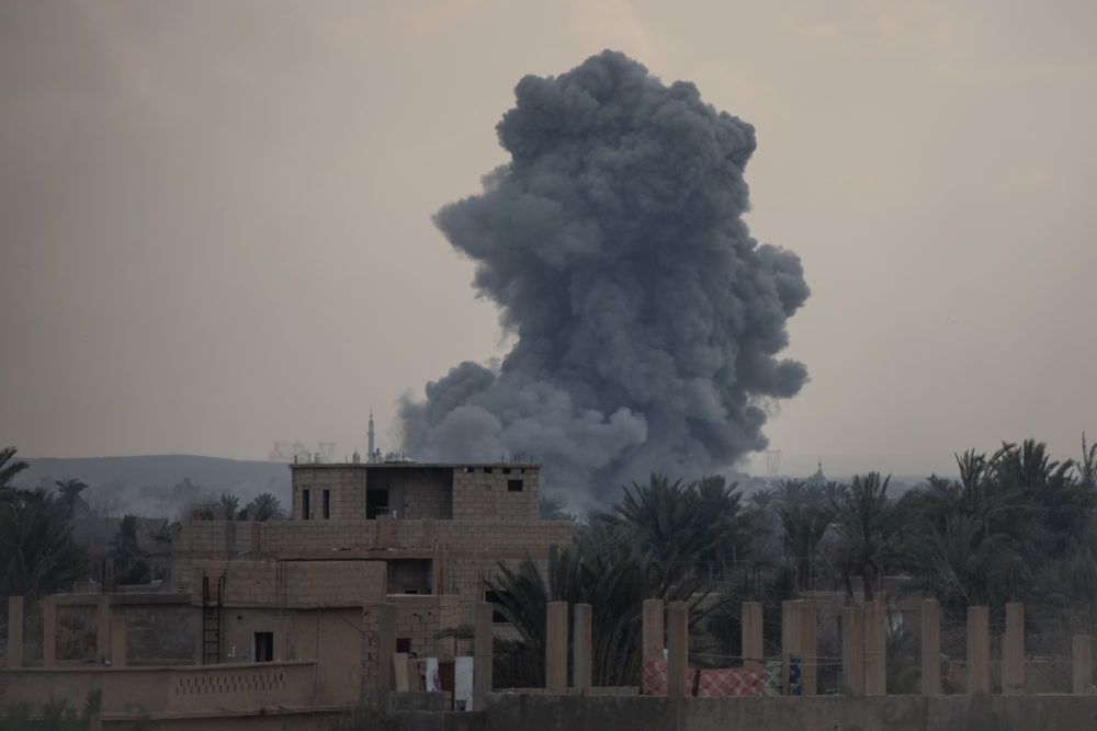 Smoke from a U.S.-led coalition airstrike is seen over buildings near the front line on February 10, 2019 in Bagouz, Syria. (Chris McGrath/Getty Images)