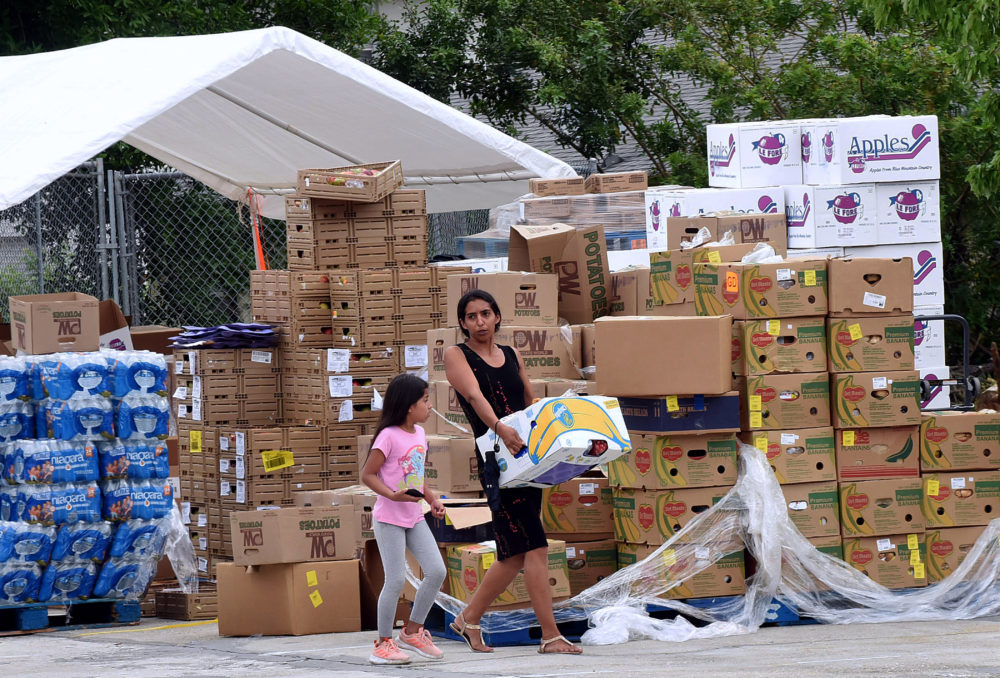 A woman with a child carries a box of food assistance she received from the Second Harvest Food Bank of Central Florida. (Paul Hennessy/NurPhoto via Getty Images)