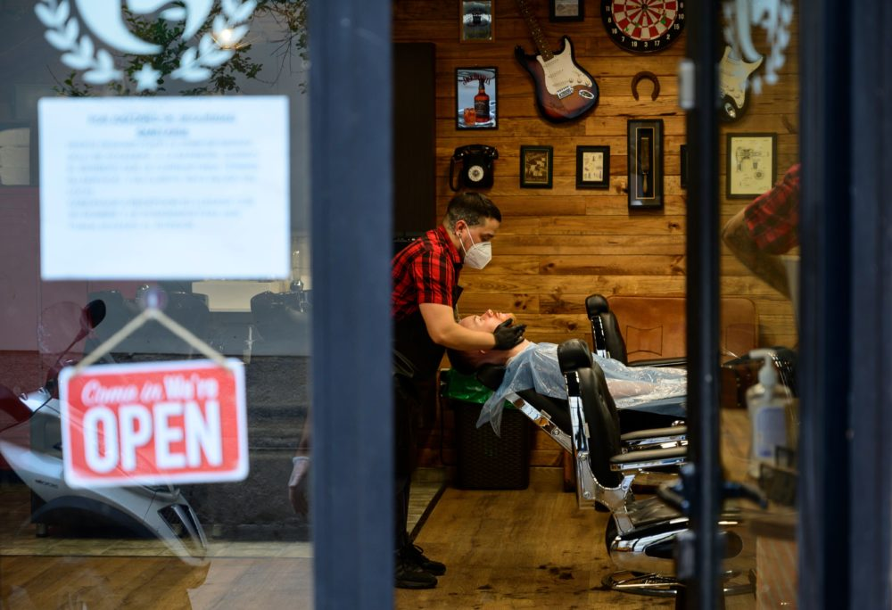 A barber attends a client after reopening his barber shop on May 4, 2020. (Pierre-Philippe Marcou/AFP via Getty Images)