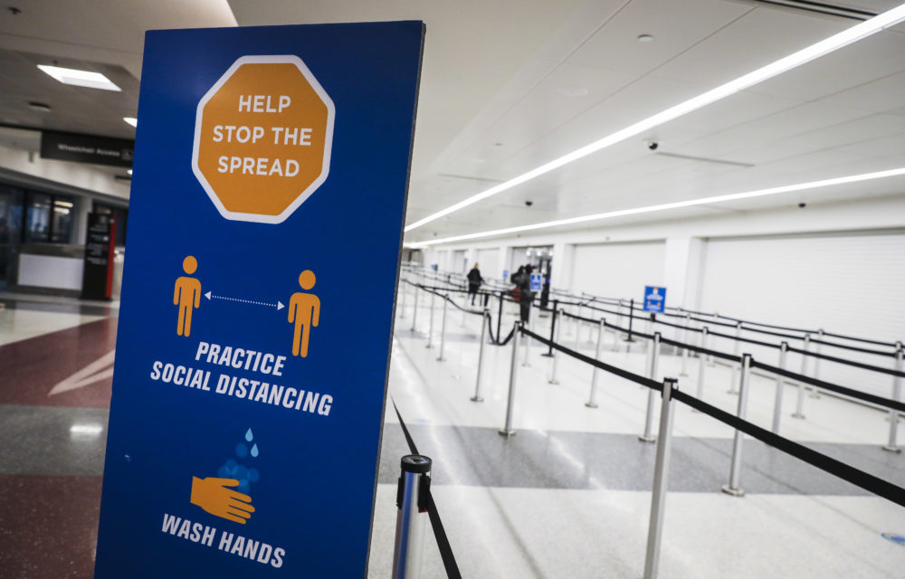 A sign encouraging people to stop the spread of coronavirus sits at a nearly empty security checkpoint at Logan International Airport in Boston on Nov. 27, 2020. (Erin Clark/The Boston Globe via Getty Images)