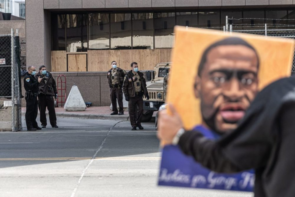 A demonstrator holds a portrait of George Floyd outside the Hennepin County Government Center in Minneapolis, Minnesota. The high-profile trial of former officer Derek Chauvin began on March 29. (Kerem Yucel/AFP/Getty Images)