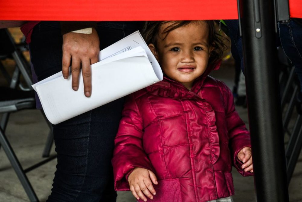 A migrant girl from Central America waits with her mother for a bus after they are dropped off by the US Customs and Border Protection at a bus station near the Gateway International Bridge, between the cities of Brownsville, Texas, and Matamoros, Mexico, on March 15, 2021 in Brownsville, Texas. (Chandian Khanna/AFP via Getty Images)