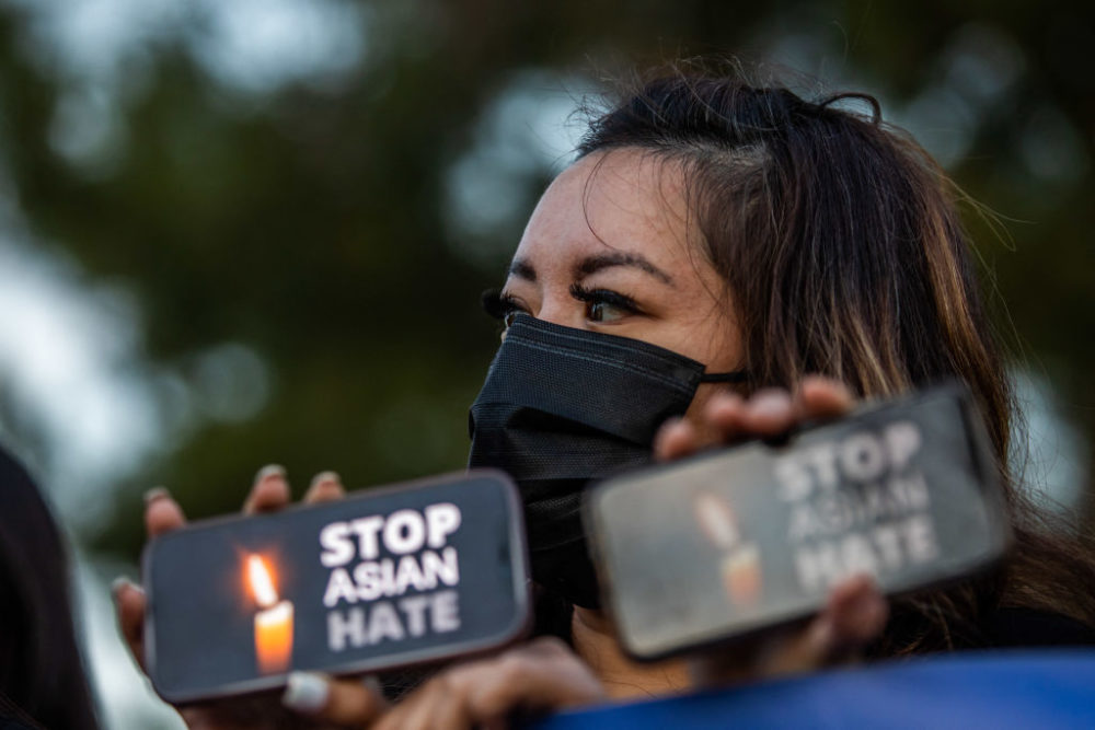 Clover Tran holds her phone during a candlelight vigil in Garden Grove, California, on March 17, 2021 to unite against the recent spate of violence targeting Asians, and to express grief and outrage after yesterday's shooting that left eight people dead in Atlanta, including at least six Asian women. (APU GOMES/AFP via Getty Images)