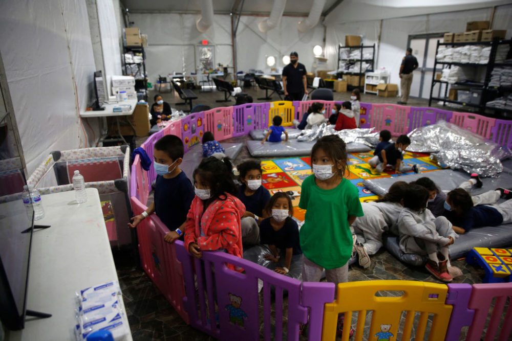 Young unaccompanied migrants ages 3 to 9 watch TV inside a playpen at the Donna Department of Homeland Security holding facility, the main detention center for unaccompanied children in the Rio Grande Valley in Donna, Texas, on March 30, 2021. (Dario Lopez-Mills/POOL/AFP via Getty Images)