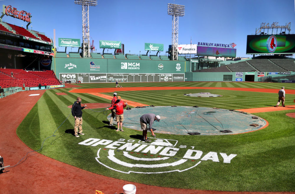 "A worker spray-paints ""Opening Day"" behind home plate at Fenway Park in Boston on March 30, 2021.  (John Tlumacki/The Boston Globe via Getty Images)"