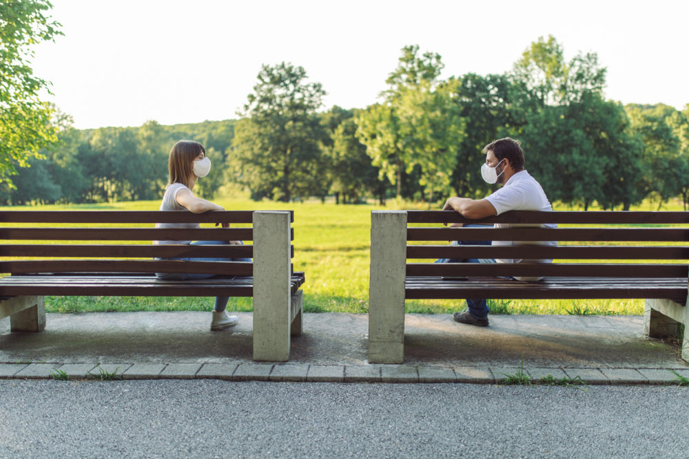 Two friends maintain social distance by sitting on separate benches and wearing protective face masks. (Getty)