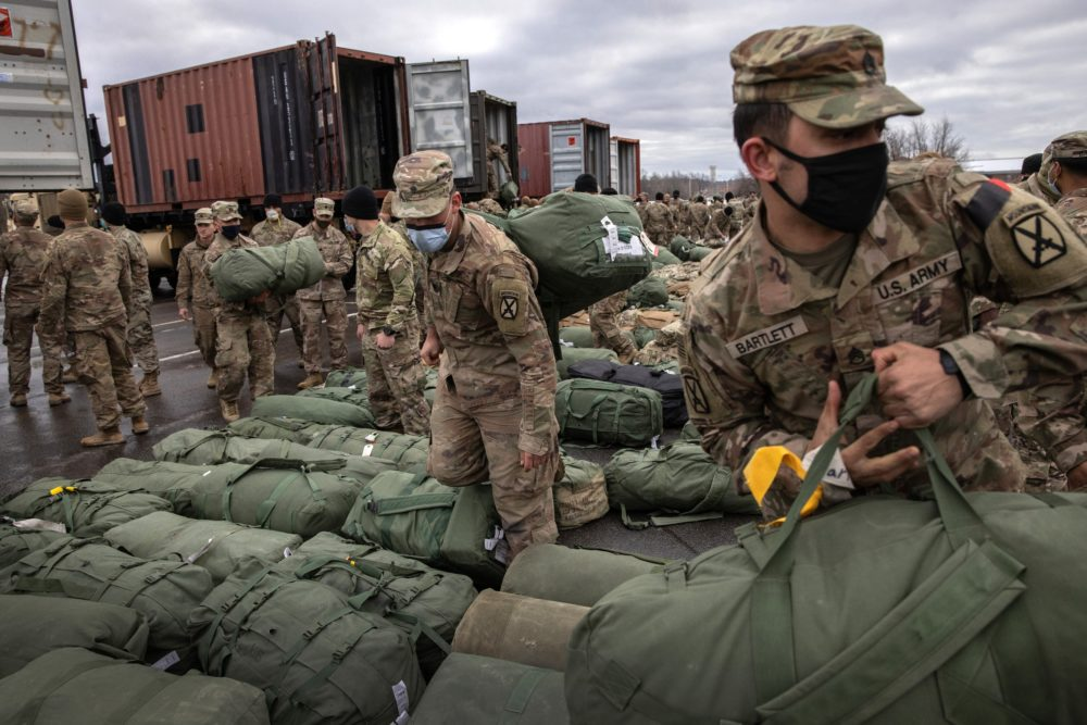 Army soldiers retrieve their duffel bags after they returned home from a nine-month deployment to Afghanistan on Dec. 10, 2020 at Fort Drum, New York. (John Moore/Getty Images)