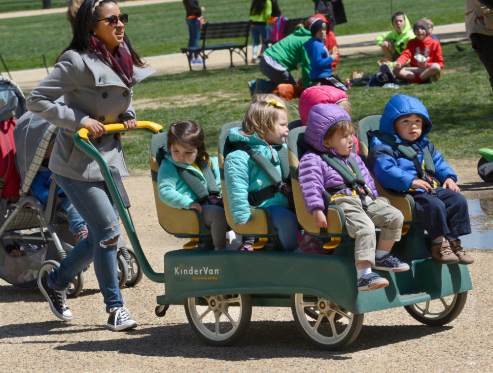A daycare center employee pushes a KinderVan filled with preschool children on an outing along the National Mall in Washington, D.C. (Robert Alexander/Getty Images)