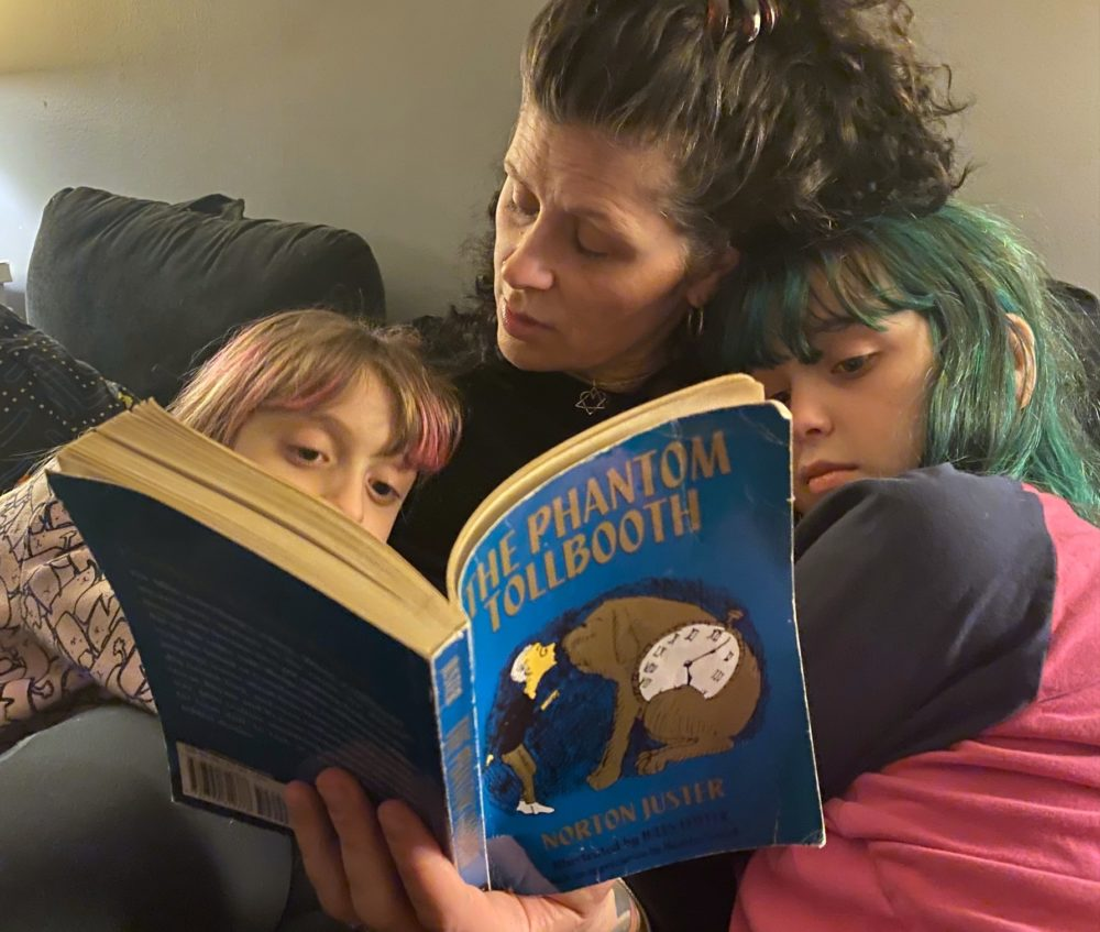"""The author reading her daughters, """"The Phantom Tollbooth,"""" in March 2021. (Courtesy)"""