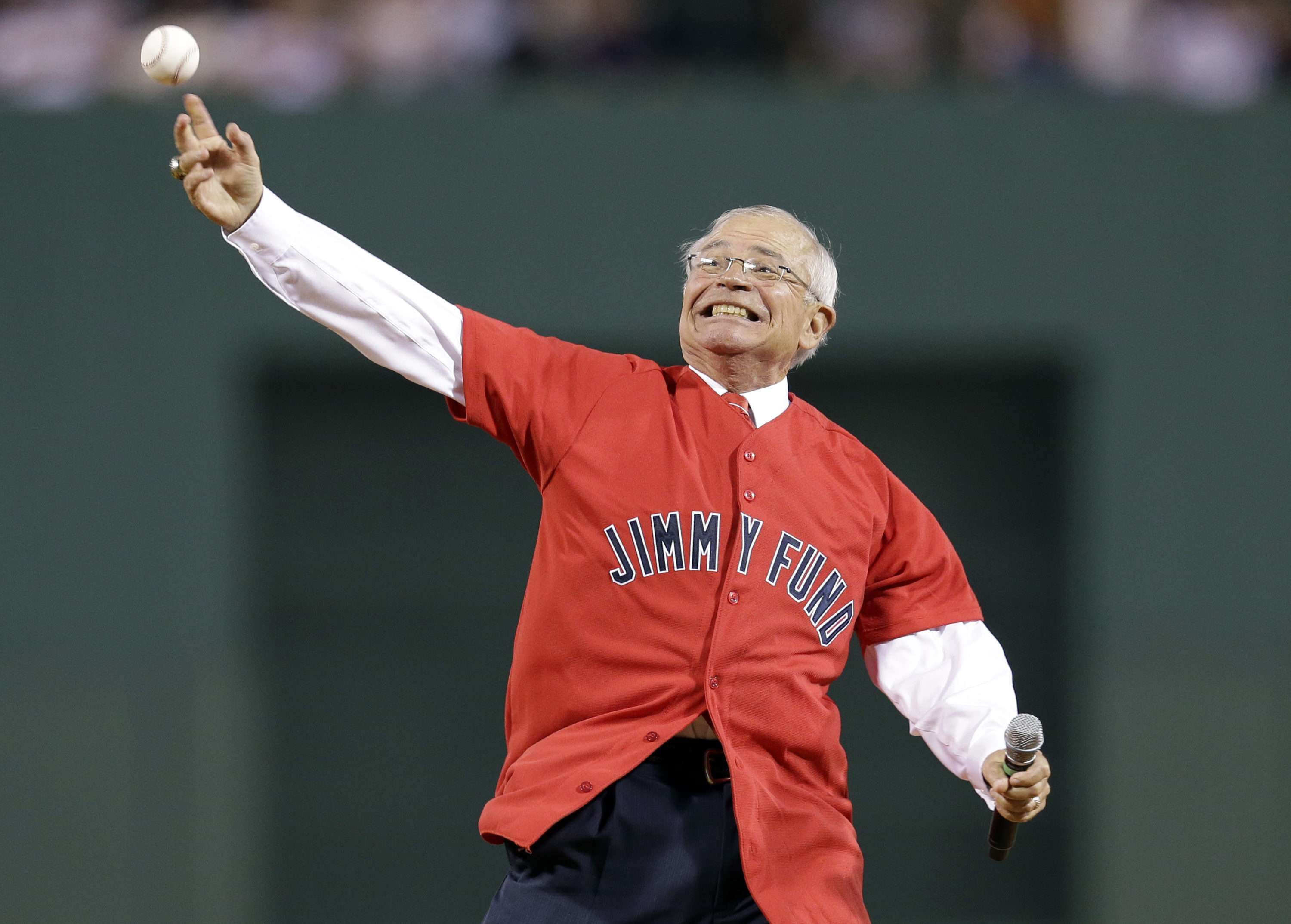 Veteran Boston Red Sox radio broadcaster Joe Castiglione throws a ceremonial first pitch prior to a baseball game against the New York Yankees at Fenway Park in Boston on Sept. 12, 2012. (Elise Amendola/AP)