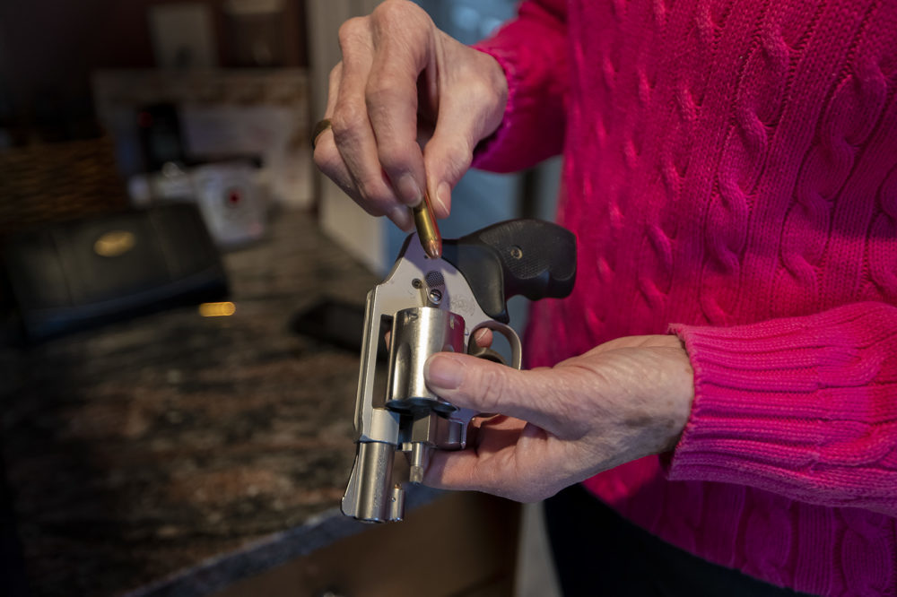 A woman loads her Smith and Wesson revolver. (Jesse Costa/WBUR)