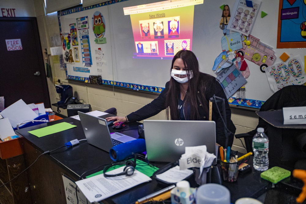 In addition to the students she has in class, Carmen Rios attends to her kindergarten students who are attending class remotely using her laptop at Barbieri Elementary School in Framingham. (Jesse Costa/WBUR)