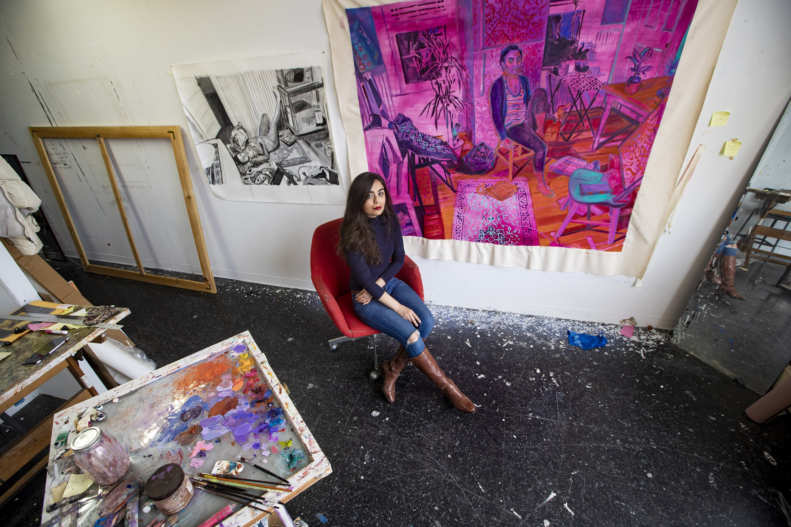 """Artist Shabnam Jannesari in front of a painting she is currently working on entitled """"62 Sidney Street"""" at her studio space at the UMass Dartmouth College of Visual and Performing Arts in New Bedford. (Jesse Costa/WBUR)"""
